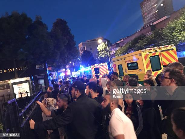 Onlookers at the scene of a huge fire as it engulfs the 24 story Grenfell Tower in Latimer Road West London as emergency services attended in the...