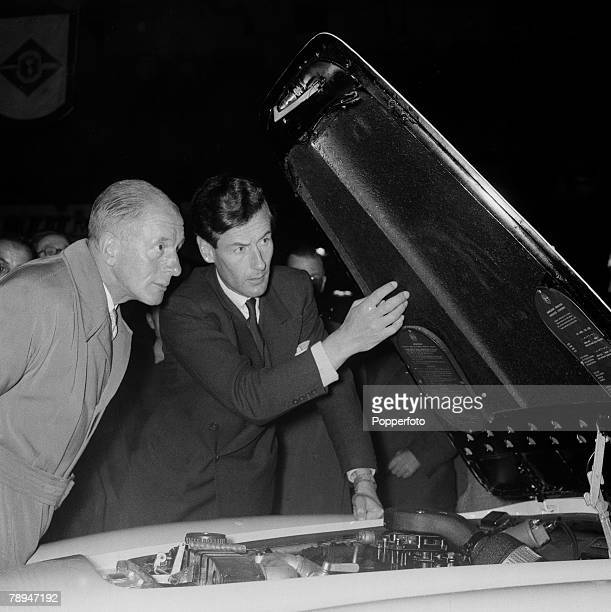 London, 18th October 1955, The Earls Court Motor Show, RAF Group Captain Peter Townsend looking under a bonnet of a car to inspect the engine
