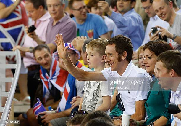 London 2012 Olympic gold medalist and 2012 Tour de France winner Bradley Wiggins of Great Britain waves as he watches the track cycling next to his...