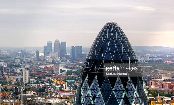 London aerial view of Gherkin skyscraper and distant view of Canary Wharf and Docklands