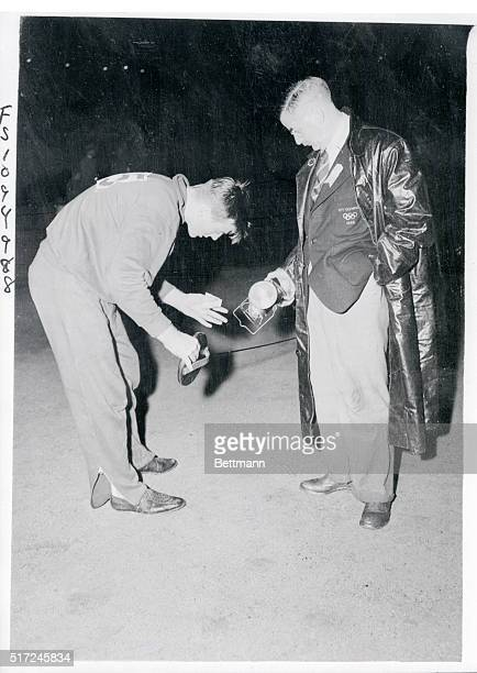 Aided by an official with a flashlight Bob Mathias 17yearold schoolboy of Tulare Calif and winner of the Decathlon measures out his run for the...
