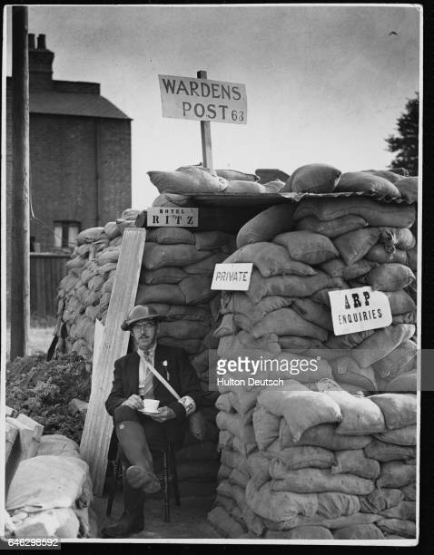 A London air raid warden drinks tea outside his sandbagged shelter