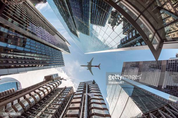 uk, london, airplane flying over modern skyscrapers on a sunny day, worm's eye view - aeroplane stock pictures, royalty-free photos & images