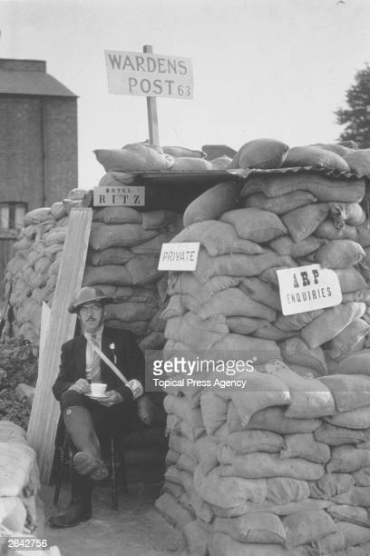 A London airraid warden on duty with a cup of tea outside a shelter