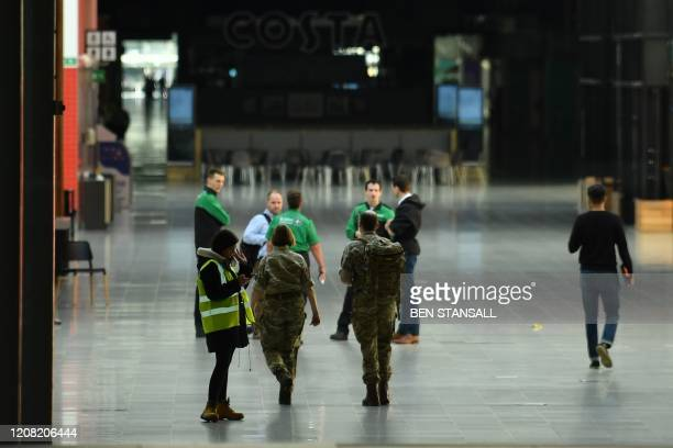 London Ambulance Service staff and personnel in military fatigues are seen inside the ExCeL London exhibition centre in London on March 25 2020 that...