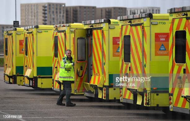A London Ambulance staff member passes ambulances parked in the car park at the ExCeL London exhibition centre in London on March 29 which has been...