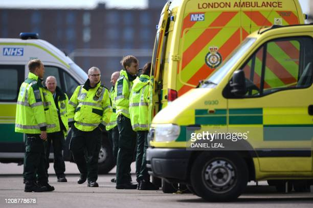 London Ambulance staff members are seen in the car park at the ExCeL London exhibition centre in London on April 1 which has been transformed into...