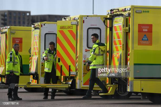 London Ambulance staff members are seen with vehicles in the car park at the ExCeL London exhibition centre in London on April 1 which has been...