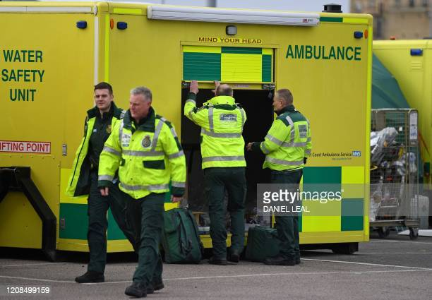 London Ambulance staff walk past amblulances parked in the car park at the ExCeL London exhibition centre in London on March 29 which has been...
