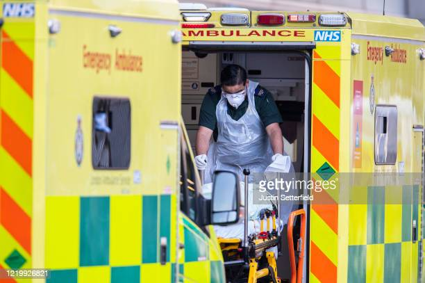 London Ambulance worker takes a patient with an unknown condition from an ambulance outside of the Royal London Hospital on April 20 2020 in London...