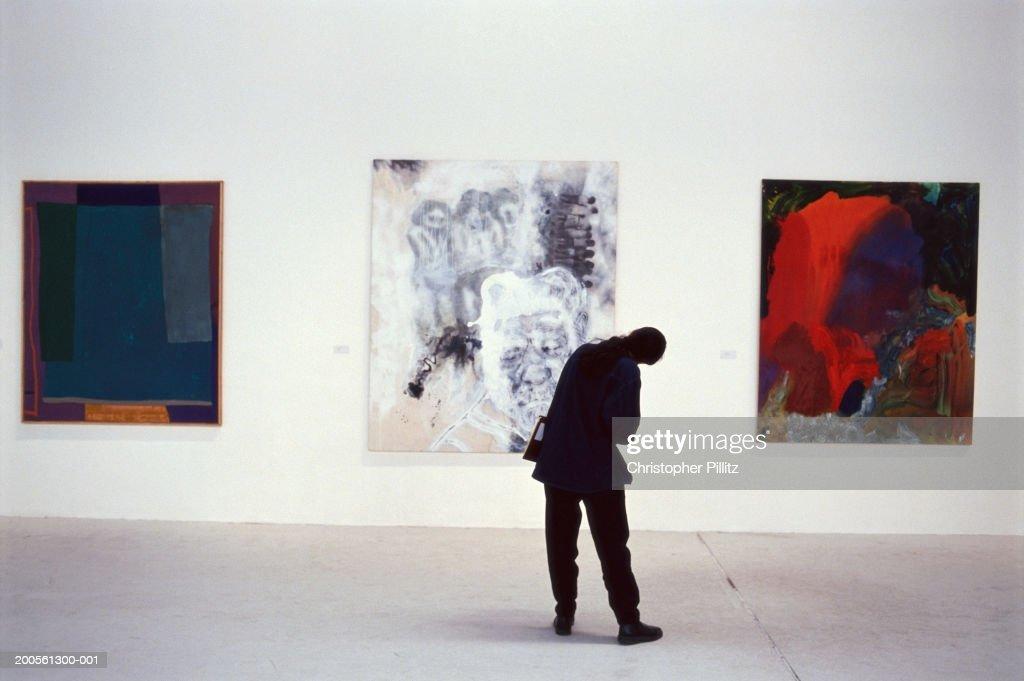 UK, London, Atlantis Gallery, person looking at artwork, rear view : Stock-Foto