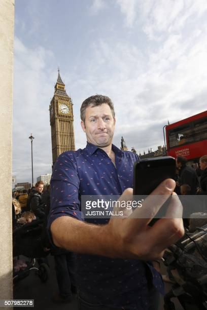 Australian comedian and television presenter Adam Hills poses for a portrait in front of Big Ben in London on February 16 2013 AFP PHOTO / JUSTIN...