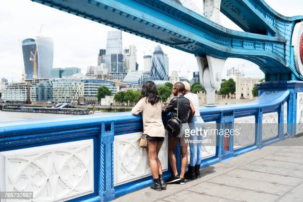 UK, London, back view of three friends looking at skyline