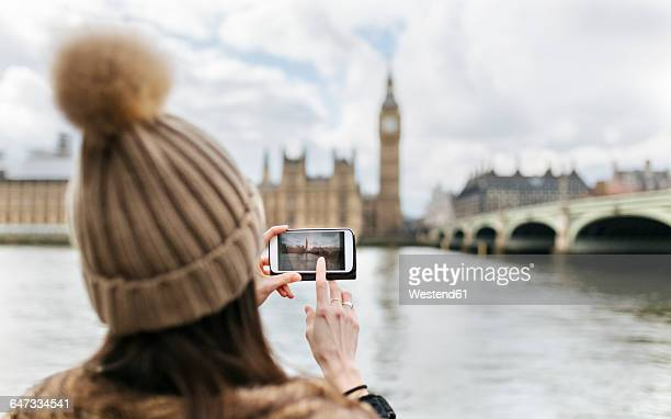 UK, London, back view of young woman taking picture of Westminster Parliament
