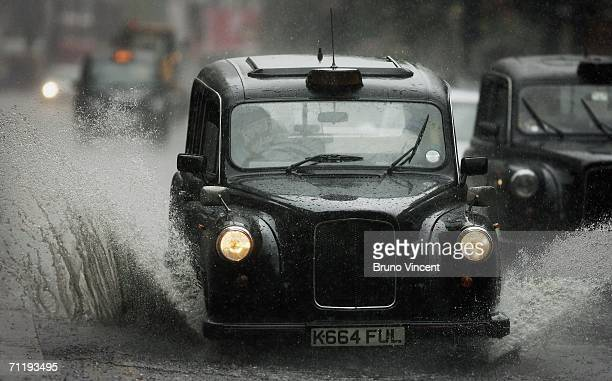 London 'Black Cab' taxi drives through a patch of standing water after a heavy downpour on June 13 2006 in London