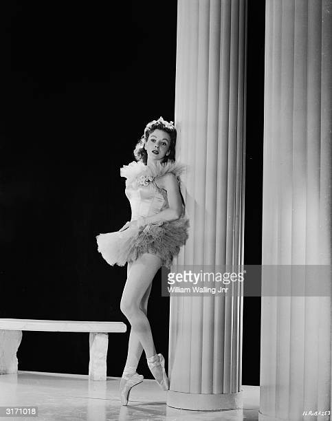 London born actress Ida Lupino leaning against a pillar wearing a tutu and ballet shoes.