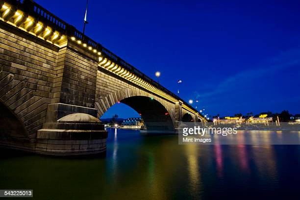 london bridge at night, spanning the waters of lake havasu. reflections in calm water.  - lake havasu stock photos and pictures