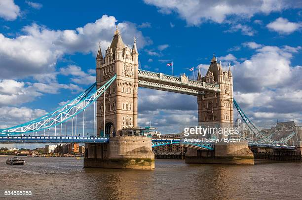 london bridge over thames river against cloudy sky - london bridge stock photos and pictures
