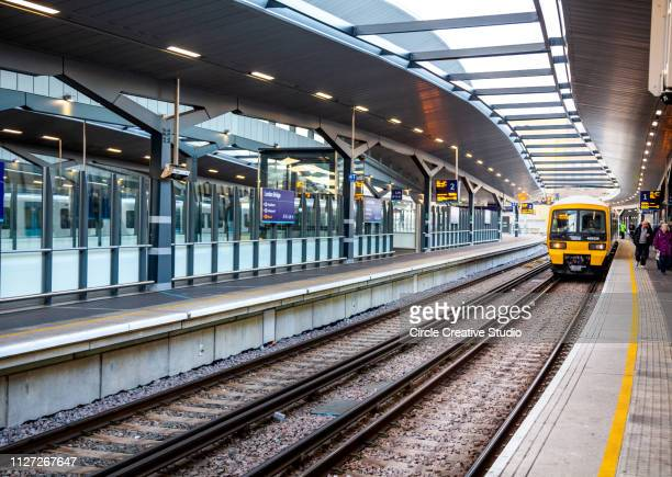 london bridge station with train and travellers - london bridge stock photos and pictures