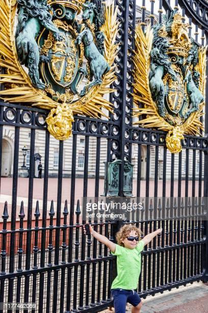 London Buckingham Palace Gate royal coat of arms gate and boy posing