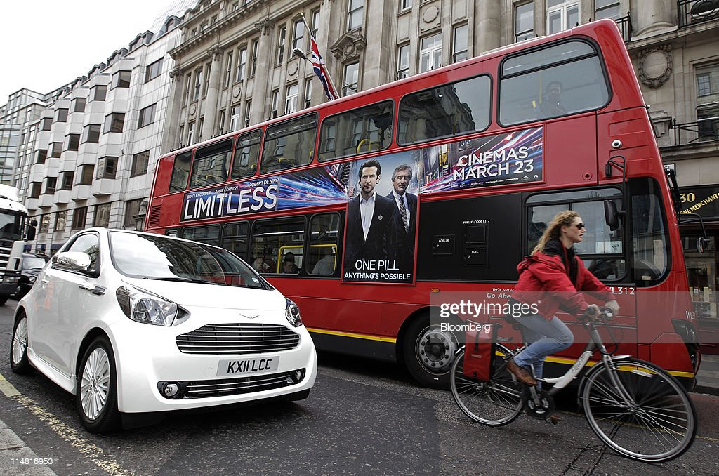 A London Bus And A Cyclist Pass An Aston Martin Cygnet, Left, As It