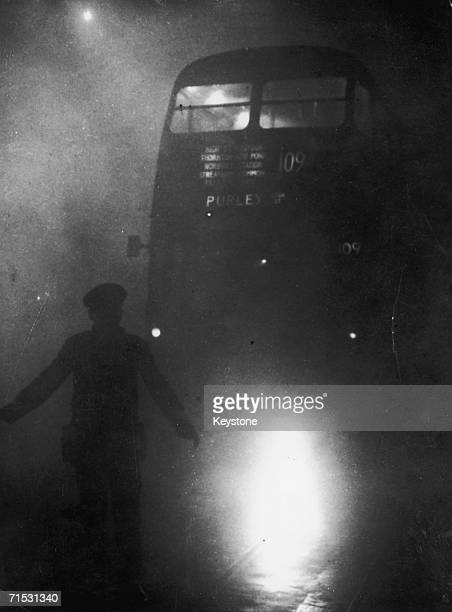 A London bus conductor is forced to walk ahead of his vehicle to guide it through the smog 9th December 1952