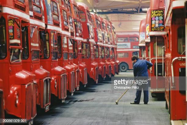 UK, London, Bus depot, man sweeping floor