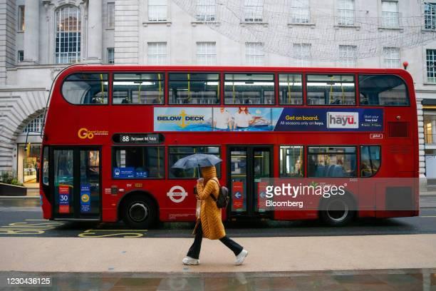 London bus passes a pedestrian walking along Regent Street in London, U.K., on Tuesday, Jan. 5, 2021. U.K. Prime Minister Boris Johnson pinned his...