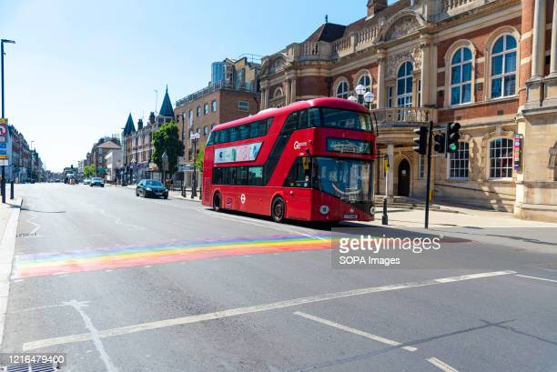London Bus waits at Wandsworths first permanent rainbow crossing to show support for the borough's LGTBQ+ community outside the iconic Battersea Arts...
