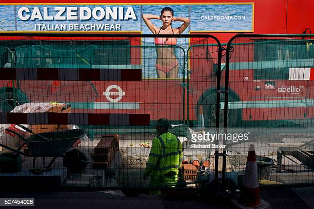 London bus with side advert for Italian swimwear label Calzedonia stopped at lights by construction work in central London Green netting separates...