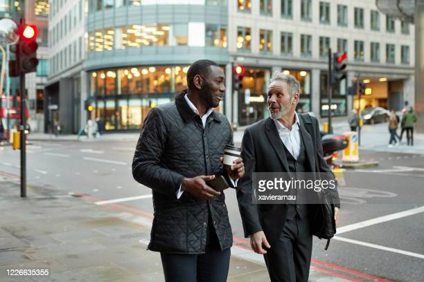 london business colleagues walking and talking after work - downtown stock pictures, royalty-free photos & images