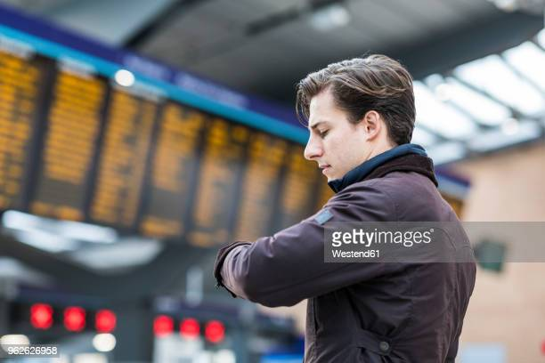 UK, London, businessman at train station checking the time