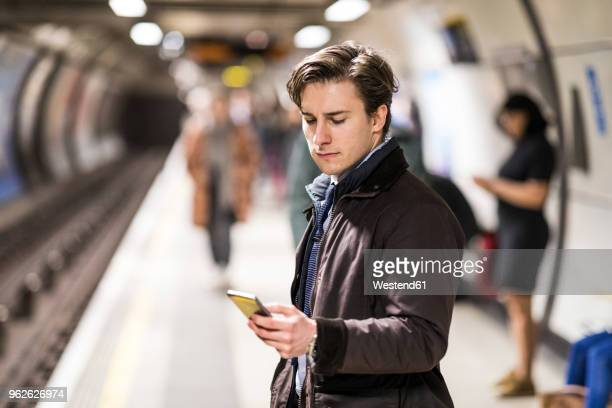 uk, london, businessman waiting at underground station using cell phone - vertical red tube fotografías e imágenes de stock