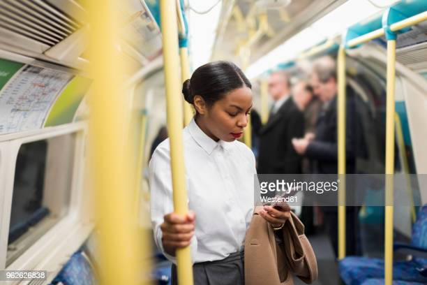 uk, london, businesswoman in underground train looking at cell phone - foco diferencial imagens e fotografias de stock