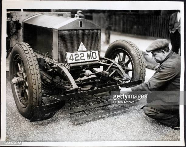 London busman Mr William Lloyd demonstrates his invention a 'cowcatcher' for meter cars and buses in London England He claims that anybody falling in...