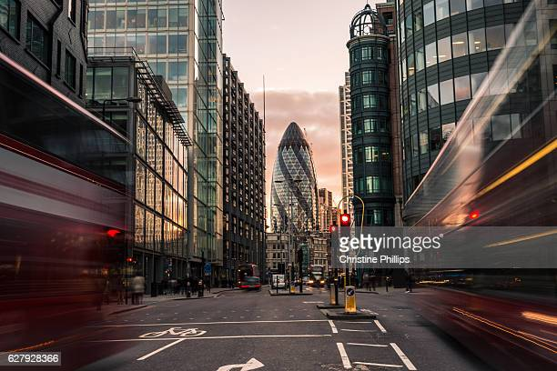 London busses rush to and from St Mary Axe in the Financial District of the City of London