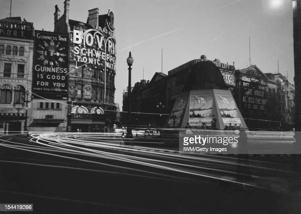 London By Moonlight The headlamps of cars streak through the darkness as they travel around Piccadilly Circus in London Several pedestrians are just...