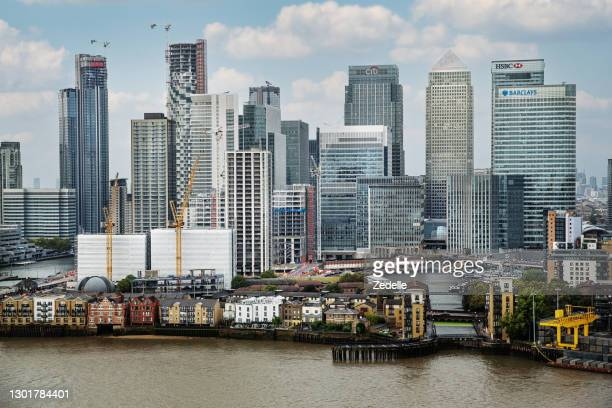 london canary wharf skyline and the river thames - building exterior stock pictures, royalty-free photos & images