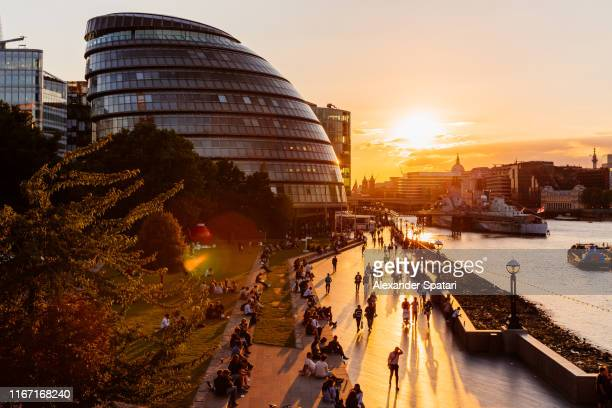london city hall and people walking along thames river at sunset, london, england, uk - flussufer stock-fotos und bilder