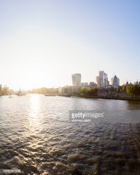 london city skyline across thames river at sunset - flussufer stock-fotos und bilder
