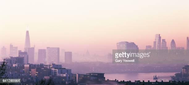 london city skyline and river thames in the fog - zachtroze stockfoto's en -beelden