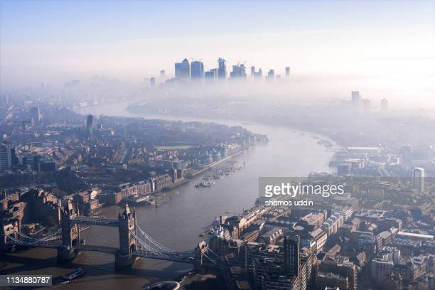 london city skyline shrouded in fog - aerial view - isle of dogs london stock pictures, royalty-free photos & images