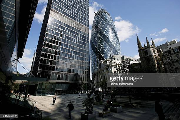 London city workers walk betwen buildings as 30 St Mary's Axe knicknamed The Gherkin is pictured on September 18 2006 in London England The famous...