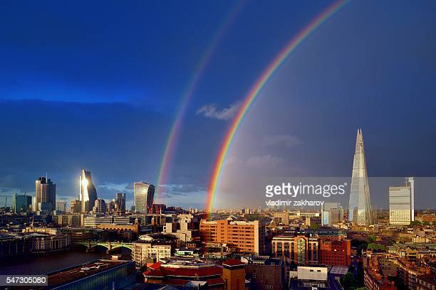 London cityscape after rain with double rainbow in dark sky