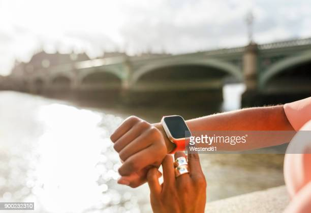uk, london, close-up of woman using her smartwatch near westminster bridge - wrist watch stock pictures, royalty-free photos & images