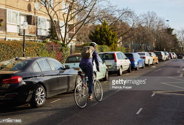 london cycle commuter riding away in neighborhood on way to work. - city stock pictures, royalty-free photos & images