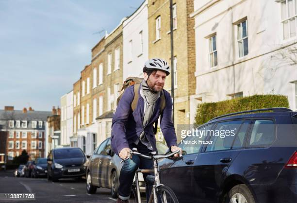 london cycle commuter riding in neighborhood on way to work. - cycling stock pictures, royalty-free photos & images
