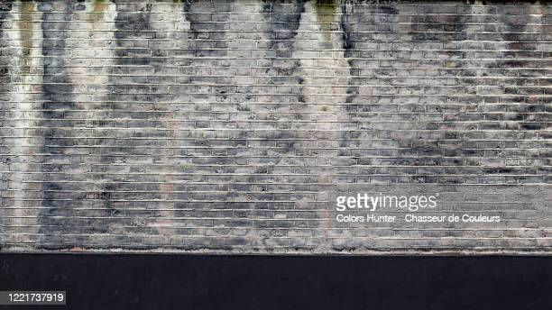 london dirty brick and black concrete wall with patina - grey stock pictures, royalty-free photos & images