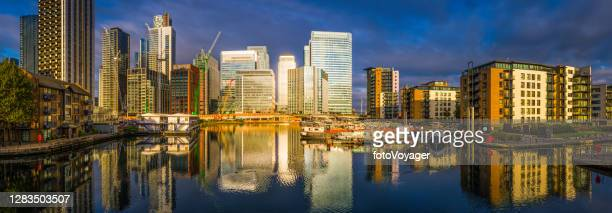 london docklands canary wharf skyscrapers dawn sunlight glow panorama uk - flat stock pictures, royalty-free photos & images