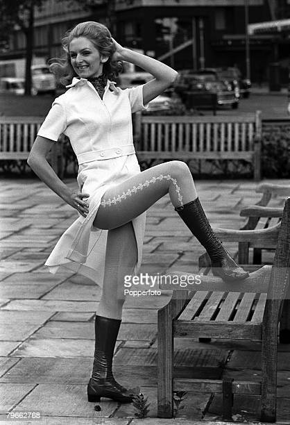 London, England, 10th September 1970, A model stands by a bench with her foot placed on the armrest to display the split skirt and patterned tights...